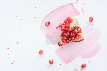 top view of pomegranate on white surface with pink watercolor strokes
