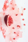 top view of tasty pomegranate on white surface with red watercolor strokes