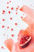 top view of tasty pomegranate piece with seeds on white surface with red watercolor strokes