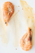 top view of delicious shrimps on white tabletop with watercolor strokes