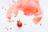 top view of single cherry tomato on white surface with red watercolor strokes