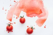 top view of fresh cherry tomatoes on white surface with red watercolor strokes and blots