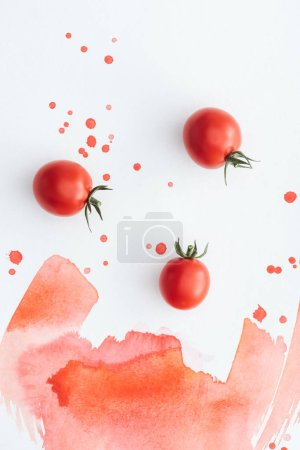 top view of ripe cherry tomatoes on white surface with red watercolor strokes and blots