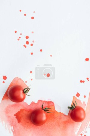 top view of cherry tomatoes on white surface with red watercolor strokes and blots