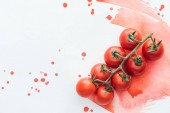 top view of branch of delicious cherry tomatoes on white surface with red watercolor strokes