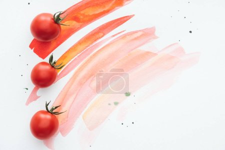 Photo for Top view of row of cherry tomatoes on white surface with red watercolor strokes - Royalty Free Image
