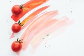 top view of row of cherry tomatoes on white surface with red watercolor strokes