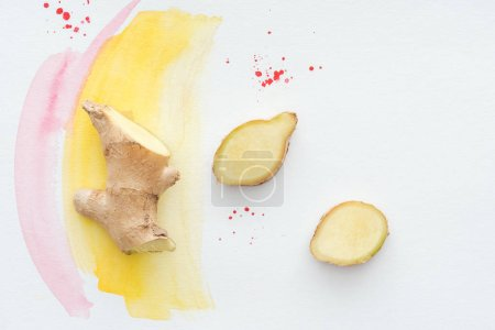 top view of sliced ginger root on white surface with yellow watercolor strokes