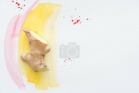 top view of half of ginger root on white surface with yellow watercolor strokes
