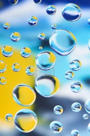 Foto de Vista cercana de agua limpia hermosa cae sobre fondo abstracto colorido borroso - Imagen libre de derechos
