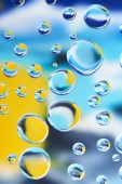 close-up view of beautiful clean water drops on blurred colorful abstract background