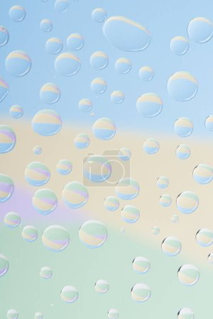 close-up view of transparent rain drops on light abstract background
