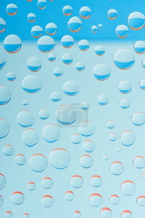 close-up view of transparent droplets on light blue background