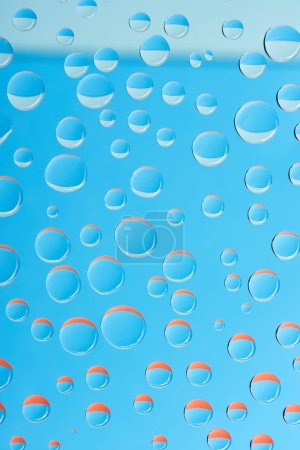 close-up view of transparent water drops on bright blue background