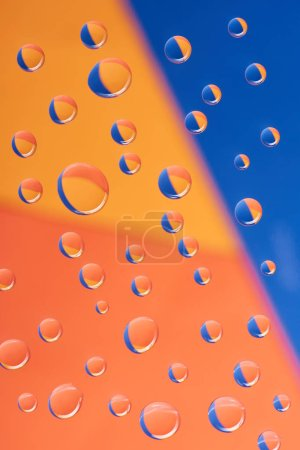close-up view of transparent water drops on colorful background