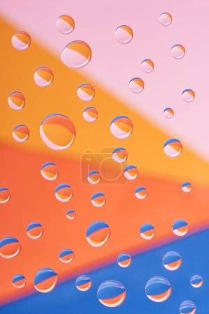 close-up view of transparent calm water drops on colorful background