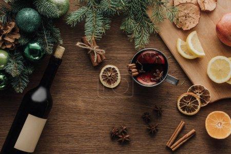 Foto de Vista superior de la taza de vino caliente con especias y frutas en madera mesa, concepto de Navidad - Imagen libre de derechos