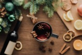 top view of cup of homemade mulled wine with cinnamon sticks on wooden tabletop, christmas concept