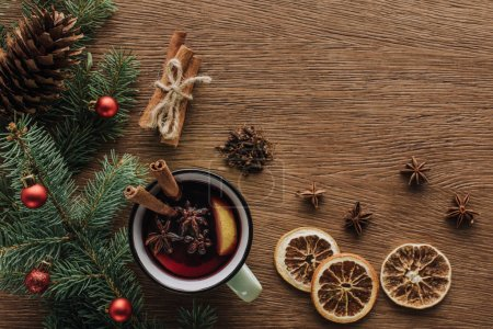top view of mulled wine, dried oranges and fir twigs with baubles on wooden tabletop, christmas concept