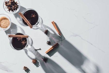 vue du dessus des verres de vin chaud et oeillet sur table blanche
