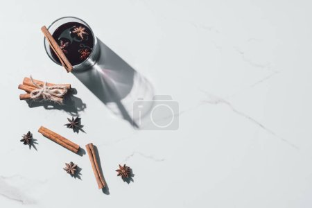 elevated view of mulled wine in glass and scattered cinnamon sticks on white tabletop