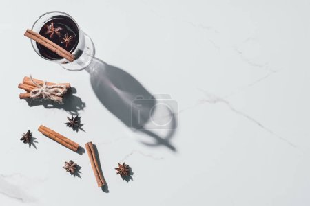 elevated view of glass of mulled wine, carnation and cinnamon sticks on white tabletop