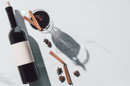 Photo for Top view of mulled wine in glass and wine bottle on white tabletop - Royalty Free Image