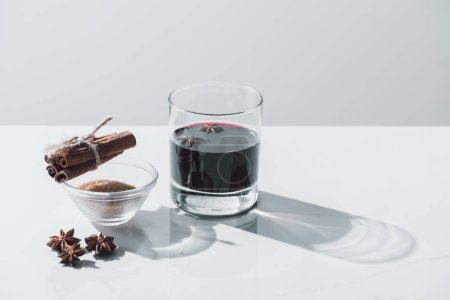 Photo for Mulled wine in glass, cinnamon sticks and brown sugar on white tabletop - Royalty Free Image