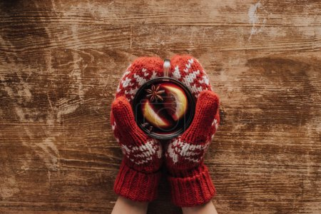 Photo for Cropped image of woman in mittens holding glass of mulled wine at wooden tabletop, christmas concept - Royalty Free Image