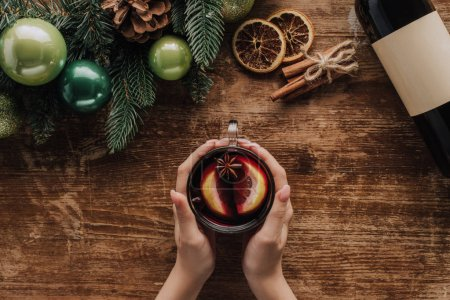 Photo for Cropped image of woman holding glass of mulled wine at wooden tabletop, christmas concept - Royalty Free Image