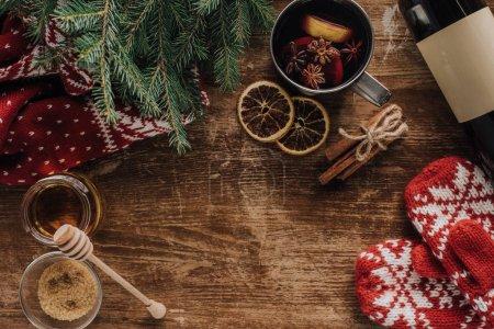 Photo pour Vue de dessus du vin chaud en coupe et mitaines en bois table, concept de Noël - image libre de droit