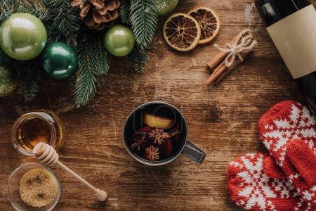 Foto de Vista elevada de taza de vino caliente y mitones de invierno en la mesa de madera, concepto de Navidad - Imagen libre de derechos
