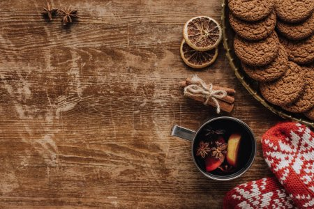 top view of mulled wine in cup, mittens and cookies on wooden tabletop, christmas concept