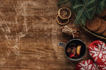 Photo for Elevated view of mulled wine in cup, mittens and cookies on wooden tabletop, christmas concept - Royalty Free Image