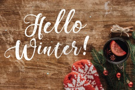 elevated view of mulled wine in cup and greeting Hello Winter on wooden tabletop, christmas concept