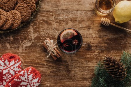 Photo for Top view of mulled wine in cup, mittens, fir twigs and honey on wooden tabletop, christmas concept - Royalty Free Image
