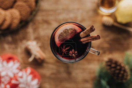 top view of mulled wine with cinnamon sticks and lemon in glass on wooden tabletop, christmas concept