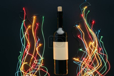 top view of wine bottle and garland lights with long exposure isolated on black, christmas concept