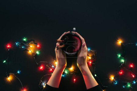 cropped image of woman holding cup of mulled wine near garland isolated on black, christmas concept