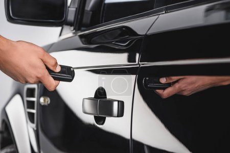 partial view of man with car key opening black automobile