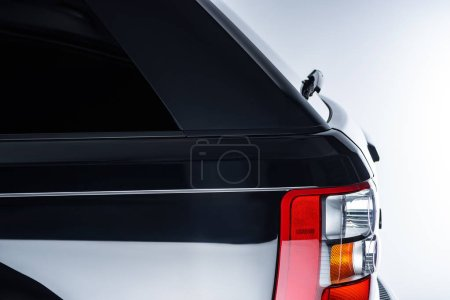 close up view of automotive head lamps of luxury black car on grey background