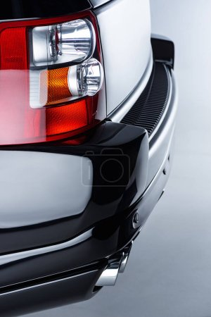Close up view of rear headlight of luxury black car on grey backdrop