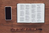 top view of opened holy bible with beads and smartphone on wooden table