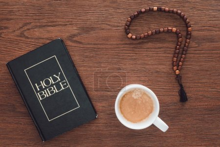 top view of holy bible with beads and coffee on wooden table