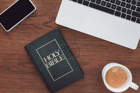 Photo for Top view of holy bible with new testament, gadgets and coffee on wooden surface - Royalty Free Image