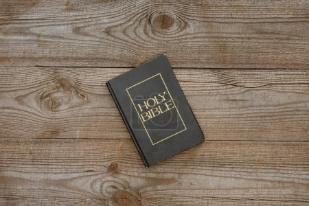 top view of holy bible on rustic wooden tabletop