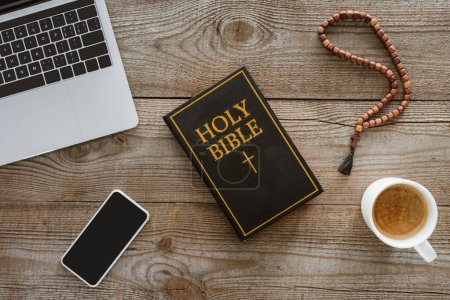 Photo for Top view of holy bible with new testament, gadgets and coffee on rustic wooden table - Royalty Free Image