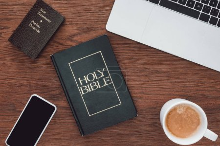Photo for Top view of holy bible with new testament, gadgets and coffee on wooden table - Royalty Free Image