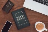 vue de dessus de la Sainte bible, nouveau testament, gadgets et café sur la table en bois