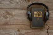 top view of holy bible with headphones on wooden surface